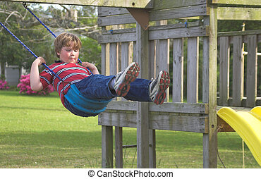 Boy on a Swing - A young boy swinging on an outdoor swingset...