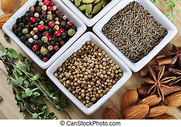 Aromatic spices in white bowls on wooden background with...