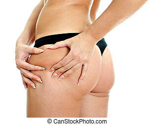 Young woman folding skin on her hips with both hands.Close...