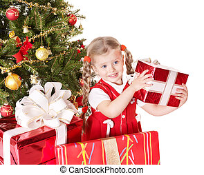 Child giving gift box by christmas tree - Happy little girl...
