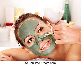 Clay facial mask in beauty spa. - Young woman with facial...