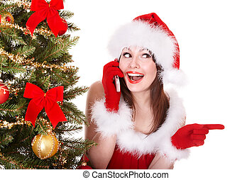Girl in Santa hat call mobile phone by christmas tree...