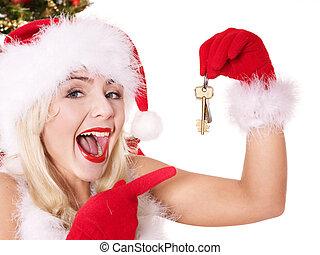Christmas girl in Santa hat holding house keys. Isolated.