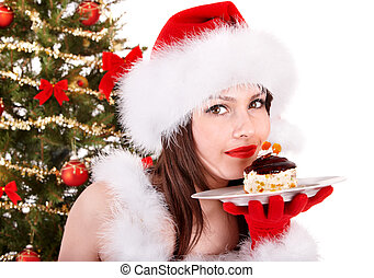 Girl in Santa hat eat cake by Christmas tree - Girl in Santa...