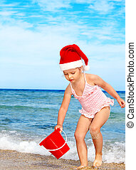 Child in Santa hat playing on beach Summer New Year