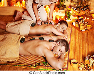 Woman and man getting stone therapy massage in spa. - Woman...