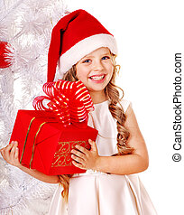 Child in Santa hat with gift box near white Christmas tree...