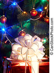 Christmas tree with flash and  gift box. Black background.