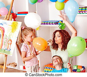 Child playing with balloon - Child with teacher inflating...