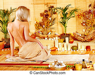 Woman getting massage in bamboo spa - Young woman getting...