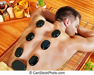 Man getting stone therapy massage . - Man getting stone...