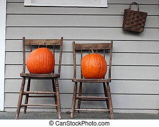Two wood chairs and orange pumpkins
