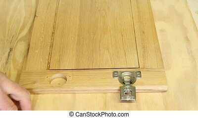 fastening cabinet hinges to a door with a drill and screws