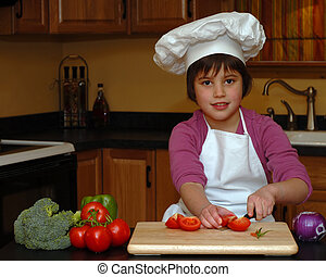 Young Cook - A young girl in a chefs hat and apron slicing...