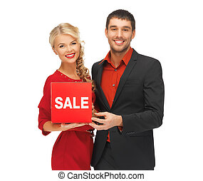 man and woman with sale sign - bright picture of man and...