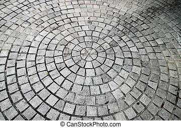 Closeup view on a cobblestone road - circle pattern -...