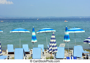 Summertime in Sirmione - Beach with colorful umbrellas in...