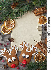 Blank note and christmas cakes on wooden background
