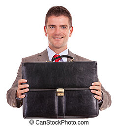 business man offering briefcase - smiling young business man...