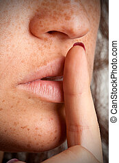 Secret - Closeup of a woman with her finger over her mouth