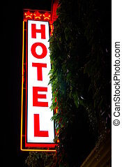 Lighted hotel sign in the night (red and white).