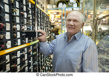 man chooses fasteners in auto parts store - mature man...