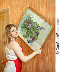 woman hangs the art picture on wall - Young woman hangs the...