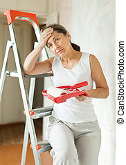 woman makes repairs at home - weariness mature woman makes...