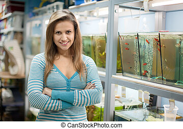 Woman near aquariums with fishes in pet-shop