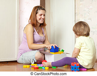 Happy mother plays with baby