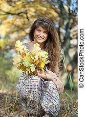 girl in autumn park - girl with oak leaves posy in autumn...
