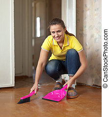 Woman sweeping the floor - Woman sweeping the floor at home...