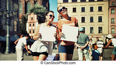 Two smiling girls holding board