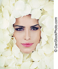 Beautiful woman face among rose petals