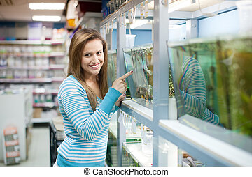 Woman chooses fish at petshop - Woman chooses fish in tank...