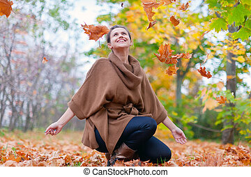 Happy girl throws maple leaves in autumn park