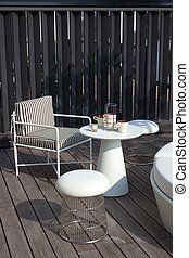 Table and chairs in a home exterior patio with wooden decking