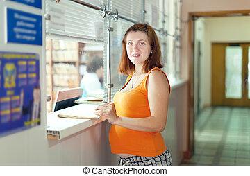 Pregnant woman in clinic reception desk - Pregnant woman...