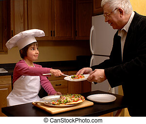 Pizza for Papa - A child-cook serving a slice of veggie...