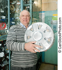 mature man buys  automotive wheel cover