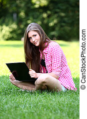 Beautiful woman with laptop in park