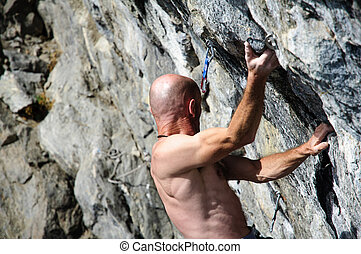 Climber while facing a wall of rock in the Alps, Northern...