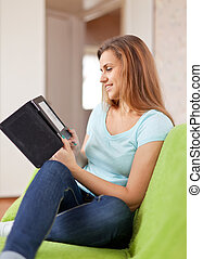 beauty woman reads e-book in home interior