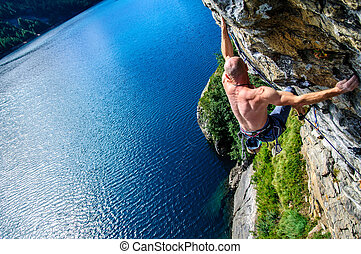Climber climbing a rock wall above Lake Devero, Northern...