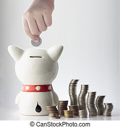 a hand saving coin in piggy bank - a hand safing coin in...