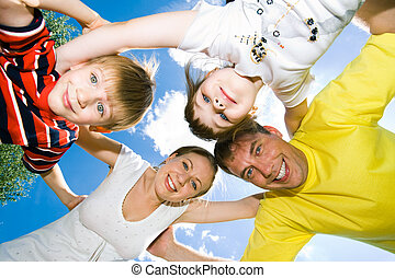 Friendship - View from below of happy family embracing each...