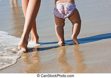 nice legs of a pretty woman walking in water  with her baby