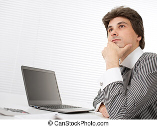 young business man thinking while working on laptop
