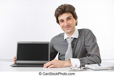 Male executive with laptop in the office