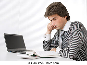 Portrait of a young businessman thinking while working on...